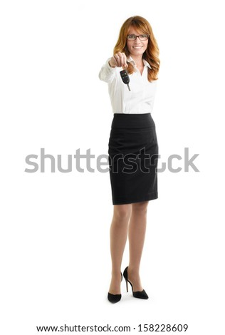 Smiling businesswoman holding up car key towards camera against white background.