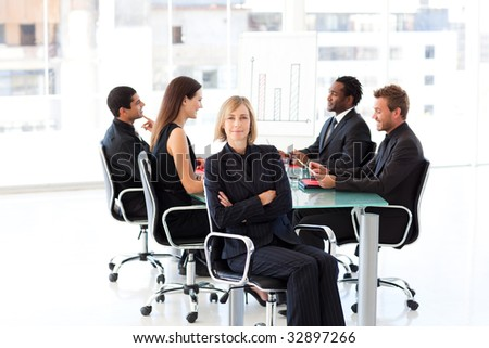 Smiling businesswoman in a meeting with her team in the background