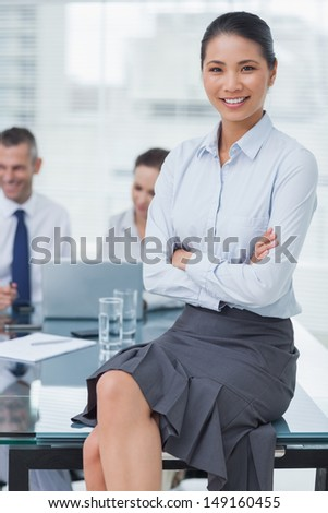 Smiling businesswoman in bright office posing with workmates on background - stock photo
