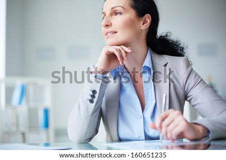 Smiling businesswoman in formalwear sitting at workplace - stock photo