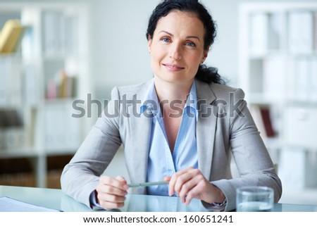 Smiling businesswoman in formalwear sitting at workplace in office - stock photo
