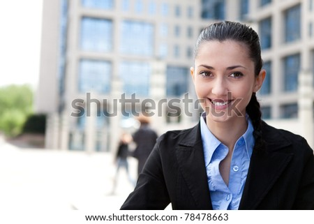 smiling businesswoman in front of office building - stock photo