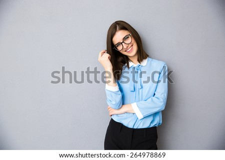 Smiling businesswoman in glasses standing over gray background. Wearing in blue shirt and glasses. Looking at camera - stock photo
