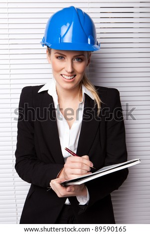 Smiling Businesswoman in Hard Hat facing camera holding a pen and notebook against white blind. - stock photo