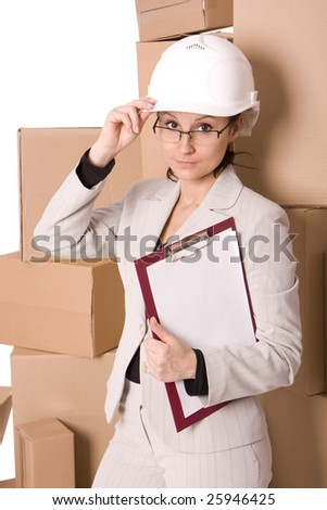 smiling businesswoman in helmet correcting glasses and keeping clipboard, on cardboard boxes background - stock photo