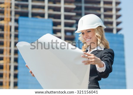Smiling businesswoman in helmet studying the sketch of future business centre. Attractive lady in business suit is satisfied by the plan made by architect.