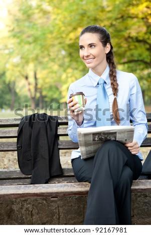 smiling businesswoman in park on cafe break - stock photo