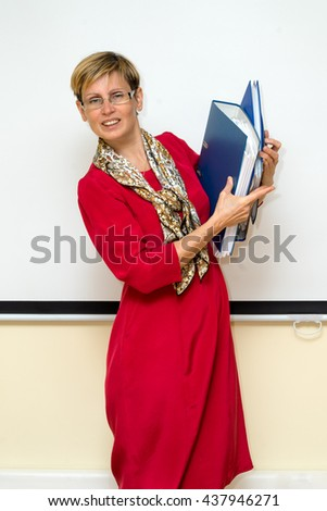 smiling businesswoman in red dress holding a folder of information and papers - stock photo