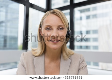 Smiling Businesswoman in the office on video conference, headset, point of view - stock photo