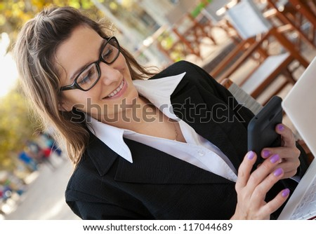 Smiling businesswoman in the outdoor cafe - stock photo