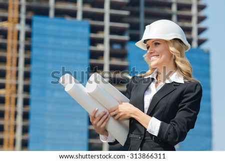 Smiling businesswoman in white helmet holding many sketches. Pretty lady in business suit is going to deliver them to her subordinates.