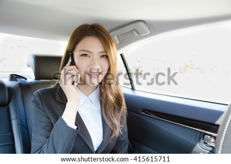smiling Businesswoman inside her car talking on the mobile phone - stock photo