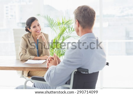 Smiling businesswoman interviewing disabled candidate in an office - stock photo