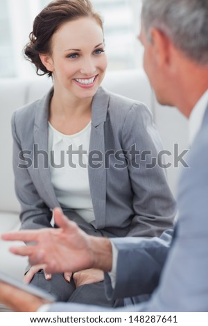 Smiling businesswoman listening to her workmate talking in bright office - stock photo