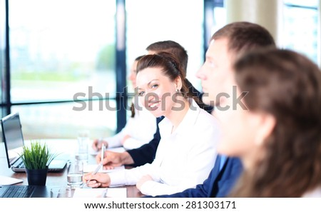 Smiling businesswoman looking at camera at seminar with her colleagues near by - stock photo
