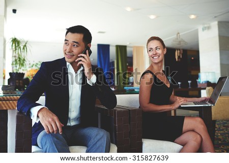 Smiling businesswoman looking at her male colleague while sitting with net-book in office, asian managing director having mobile phone conversation, professional employees preparing for the meeting - stock photo