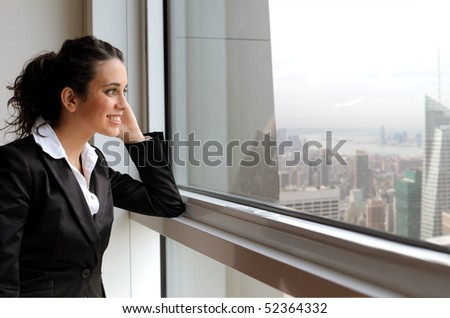 Smiling businesswoman looking out of a window - stock photo