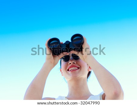 Smiling businesswoman looking through binoculars against blue sky - stock photo