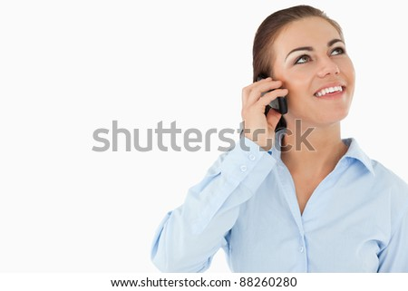 Smiling businesswoman looking upwards while on the phone against white background - stock photo