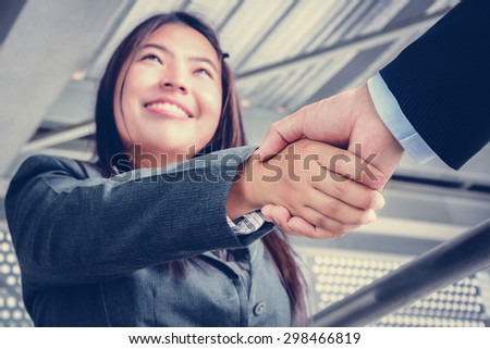 Smiling businesswoman making handshake with a businessman - stock photo