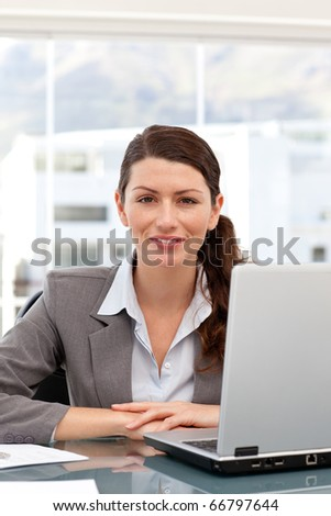 Smiling businesswoman on the computer looking at the camera in her office