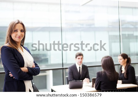 Smiling businesswoman on the foreground of his team - stock photo