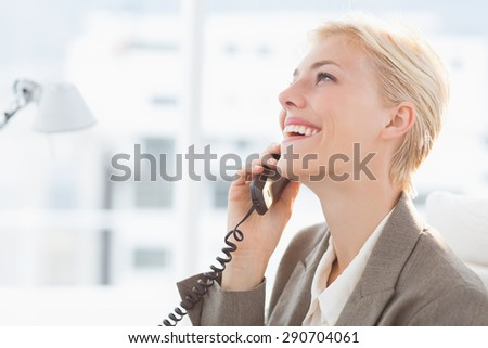 Smiling businesswoman on the phone in her desk - stock photo