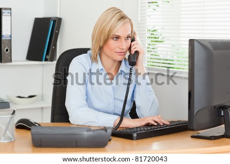 Smiling businesswoman on the phone looking at her screen in her office - stock photo