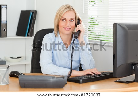 Smiling businesswoman on the phone looking into camera in her office - stock photo