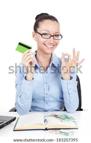 Smiling businesswoman on workplace with credit card in hand - stock photo
