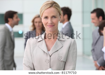 Smiling businesswoman outside with her team - stock photo