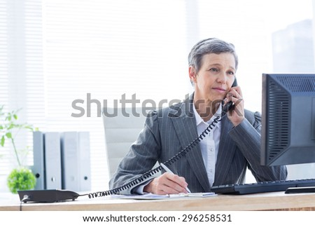 Smiling businesswoman phoning and writing at the office