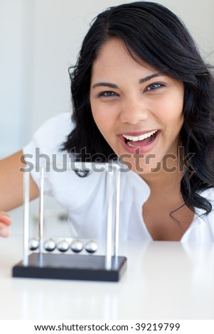 Smiling businesswoman playing with Newton balls in office - stock photo