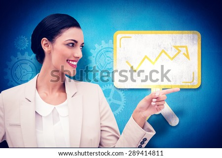 Smiling businesswoman pointing against blue background