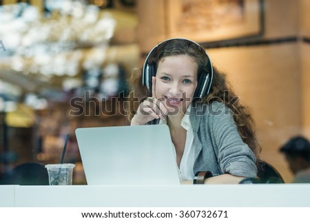 Smiling businesswoman portrait while working with her laptop and listening to music in a bar.