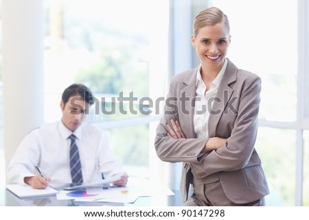 Smiling businesswoman posing while her colleague is working in a meeting room - stock photo