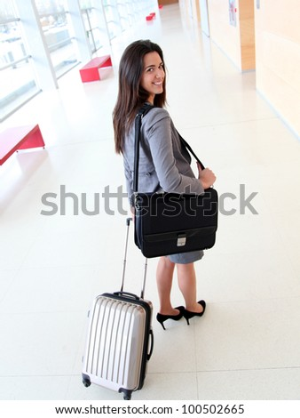 Smiling businesswoman pulling cabin suitcase in hallway - stock photo