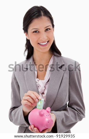 Smiling businesswoman putting money into piggy bank against a white background - stock photo