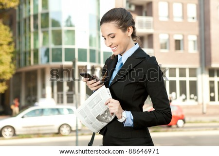 smiling businesswoman reading text message, outdoor - stock photo