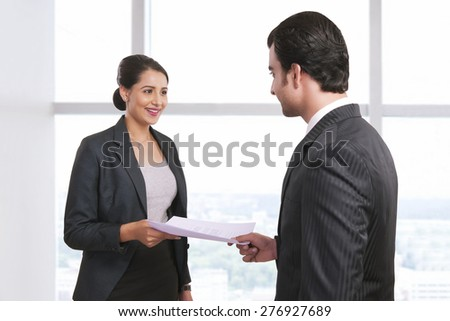 Smiling businesswoman receiving document from colleague in office