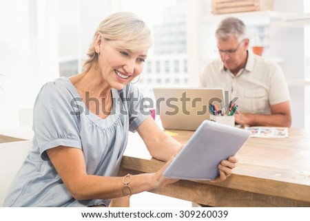 Smiling businesswoman scrolling on a tablet at office