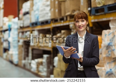 Smiling businesswoman scrolling on digital tablet in a large warehouse