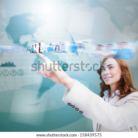 Smiling businesswoman scrolling pictures on blue map background - stock photo