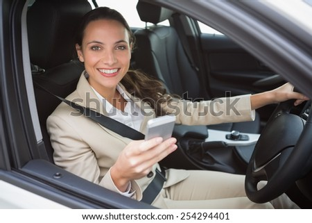 Smiling businesswoman sending a text message in her car - stock photo