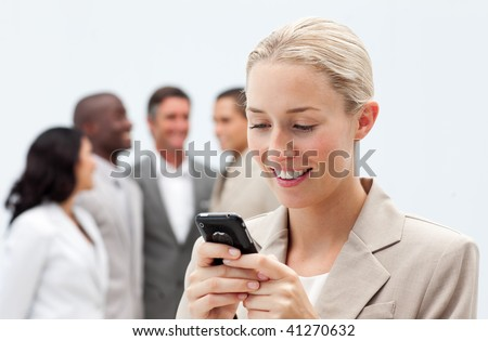 Smiling businesswoman sending a text with a mobile phone in workplace with her team in the background - stock photo
