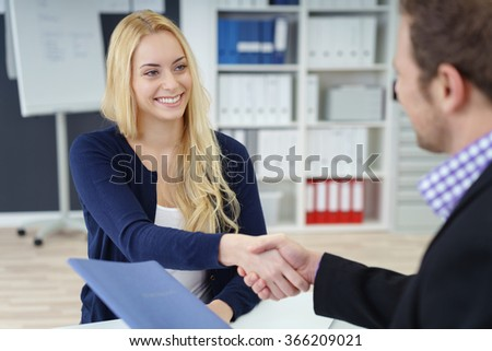 Smiling businesswoman shaking hands with a male colleague, partner or interviewer as they sit at a desk in an office with focus to her