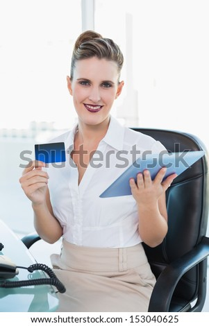 Smiling businesswoman shopping online with her tablet in her office