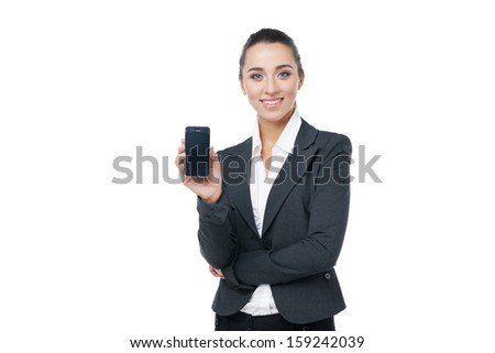 Smiling businesswoman showing cell phone. Standing isolated on white