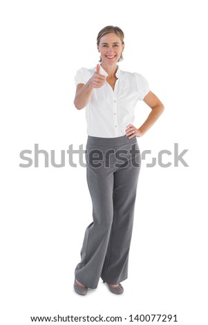 Smiling businesswoman showing her thumb up on white background - stock photo