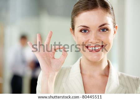 Smiling businesswoman showing sign of okay and looking at camera - stock photo